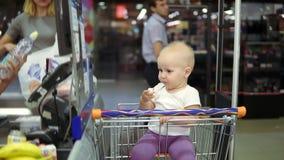 Jeune mère sortant des produits de chariot sur la bande de conveyeur au supermarché tandis que son petit bébé mignon mange banque de vidéos