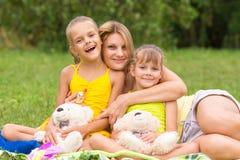 Jeune mère sur le pique-nique étreignant deux cinq et sept ans de filles, Image libre de droits