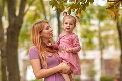 Jeune mère sur une promenade avec la fille et la feuille dans des mains image libre de droits
