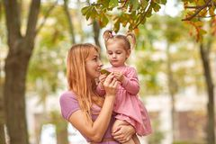 Jeune mère sur une promenade avec la fille et la feuille dans des mains Photos libres de droits