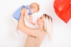 Jeune mère tenant la petite fille sur des mains et la regardant Photo stock