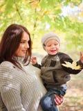 Jeune mère tenant le fils dans des bras, marchant en parc chaud d'automne Le concept de la famille image stock