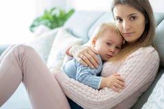 Jeune mère, tenant son garçon malade d'enfant en bas âge, l'étreignant à la maison image stock