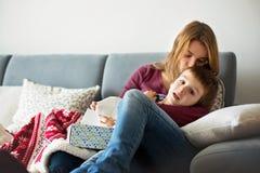 Jeune mère, tenant son petit garçon malade Photo libre de droits