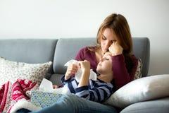 Jeune mère, tenant son petit garçon malade Images stock