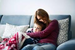 Jeune mère, tenant son petit garçon malade Image libre de droits