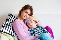 Jeune mère, tenant son petit garçon malade, tissu humide sur son avant Images libres de droits