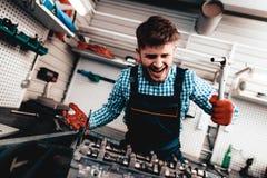 Jeune mécanicien automobile Is Screaming Station service photographie stock libre de droits