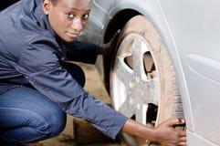 Jeune mécanicien enlevant un pneu d'une voiture Photo libre de droits
