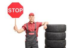 Jeune mécanicien masculin tenant un signe d'arrêt Photographie stock libre de droits