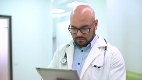 Jeune médecin avec un stéthoscope autour de son cou utilisant le comprimé numérique d'écran tactile banque de vidéos