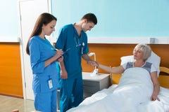 Jeune médecin masculin et infirmière féminine mesurant l'impulsion et le writi Image libre de droits
