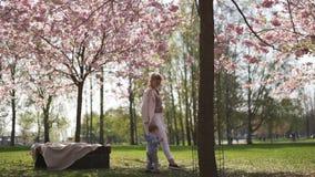 Jeune m?re marchant avec son fils d'enfant de b?b? gar?on en parc sous des arbres de Sakura clips vidéos