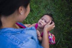 Jeune m?re ?treignant et calmant une petite fille pleurante, une m?re asiatique essayant de soulager et calmer vers le bas son en image stock