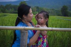 Jeune m?re ?treignant et calmant une petite fille pleurante, une m?re asiatique essayant de soulager et calmer vers le bas son en images libres de droits
