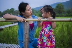 Jeune m?re ?treignant et calmant une petite fille pleurante, une m?re asiatique essayant de soulager et calmer vers le bas son en photos stock