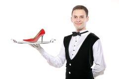 Jeune maître d'hôtel retenant un plateau avec un haut talon là-dessus image stock
