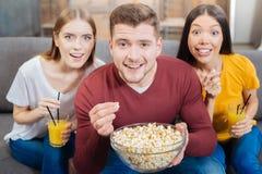 Jeune maïs éclaté mangeur d'hommes tandis que ses amis émotifs presque s'asseyant Images libres de droits