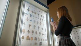 Jeune Madame dans la robe photographie par les croix antiques de téléphone dans le musée banque de vidéos