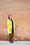 Jeune Madame devant un mur de briques Photo stock