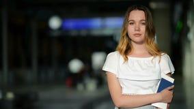 Jeune Madame mignonne avec le passeport et le billet dans des mains pose regardant l'appareil-photo l'aéroport Tableau indicateur banque de vidéos