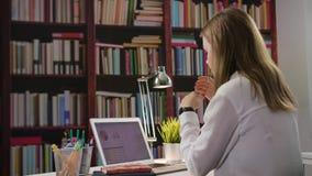 Jeune Madame Using un ordinateur portable dans la bibliothèque banque de vidéos