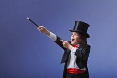Jeune magicien exécutant avec une baguette magique magique photo stock