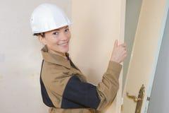 Jeune main-d'œuvre féminine avec la porte en bois Photographie stock libre de droits