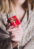 Jeune main femelle tenant le boîte-cadeau rouge simple Photographie stock