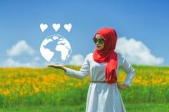 Jeune main musulmane heureuse de femme montrant la terre d'amour Photographie stock libre de droits
