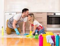 Jeune maison de nettoyage de couples ensemble et ayant des moments tendres Image stock