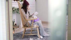 Jeune mal de tête asiatique en difficulté de sensation de femme se reposant sur une chaise enveloppée dans la couverture grise da clips vidéos