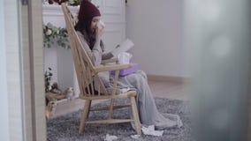 Jeune mal de tête asiatique en difficulté de sensation de femme se reposant sur une chaise enveloppée dans la couverture grise da banque de vidéos
