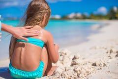 Jeune maman appliquant la crème de sunblock sur peu Image libre de droits