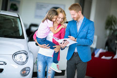 Jeune maman avec la fille dans la salle d'exposition de voiture Image libre de droits