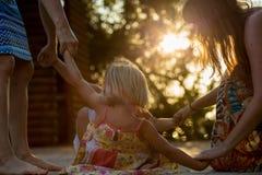 Jeune maman avec les filles blondes de fille souriant faisant l'anneau autour du rosie Lumière chaude de coucher du soleil Voyage Photographie stock libre de droits
