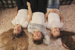Jeune maman et ses deux filles de l'adolescence se trouvant sur le plancher à la maison Photographie stock libre de droits