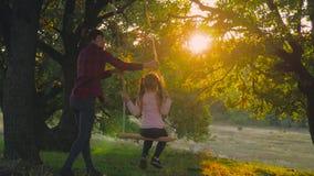 Jeune maman heureuse avec une petite fille balançant en parc ensemble au coucher du soleil Équitation de mère et de fille sur l'o banque de vidéos