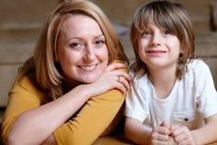 Jeune maman heureuse se trouvant sur l'étage avec son fils Photos libres de droits