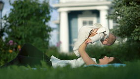 Jeune maman jouant avec sa petite fille près de la maison banque de vidéos