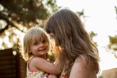 Jeune maman tenant sa fille blonde de fille sur ses bras Lumière chaude de coucher du soleil Vacances de voyage d'été de famille  Photographie stock libre de droits