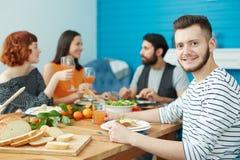 Jeune mangeur d'hommes ainsi que des amis à la maison Photo stock
