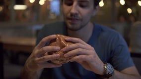Jeune mangeur d'hommes de brune attrayante un hamburger délicieux au restaurant Jeune type affamé ayant empilé l'hamburger à rapi clips vidéos