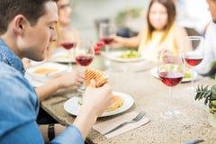 Jeune mangeur d'hommes un sandwich avec des amis Images stock