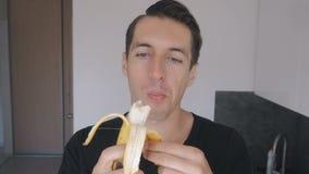 Jeune mangeur d'hommes une banane à la maison dans la cuisine banque de vidéos