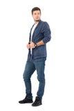 Jeune mannequin masculin dans la chemise et des jeans de denim regardant en arrière au-dessus de l'épaule tenant le collier Image stock