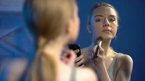 Jeune maquillage faisant femelle observant la vid?o en ligne sur le smartphone, astuces de beaut? banque de vidéos