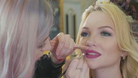 Jeune maquilleur appliquant le rouge à lèvres sur les lèvres modèles du ` s banque de vidéos