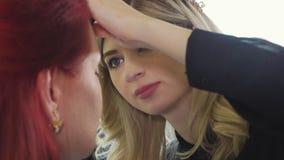 Jeune maquilleur appliquant le rouge à lèvres sur les lèvres modèles du ` s clips vidéos