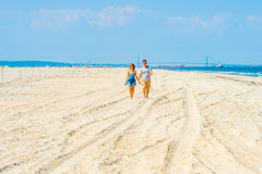 Jeune marche américaine de couples, détendant sur la plage dans nouveau Jers Photos libres de droits